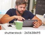 young man eating breakfast...   Shutterstock . vector #265638695