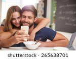 Couple Eating Breakfast Using...