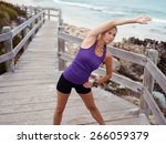 sporty young woman stretching... | Shutterstock . vector #266059379