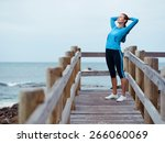 sporty young woman stretching... | Shutterstock . vector #266060069