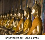 a row of seated buddhas at the...