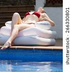 Small photo of Beautiful girl resting in air mattress near pool in summertime