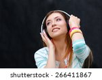 young woman listening to the... | Shutterstock . vector #266411867