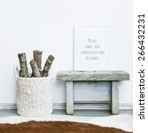 Small photo of wooden frame YOU ARE AN ADVENTURE STORY. Hipster scandinavian style room interior. Basket with firewood and a cow rug on the floor