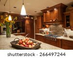 Stock photo home kitchen with island sink cabinets pendant lights stove top range and hardwood floors in 266497244