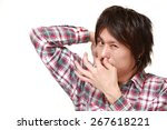 young japanese man sniffing his ... | Shutterstock . vector #267618221