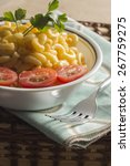 Small photo of Delicious macaroni and cheddar cheese with fresh sliced grape tomatoes and parsley sprig