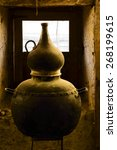 Small photo of traditional alembic distiller with window in an old adobe house sitll life