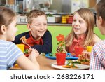 Stock photo group of pupils sitting at table in school cafeteria eating lunch 268226171