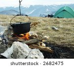 Campfire,kitchenware and tent in camping - stock photo