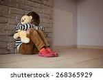 Sad Little Boy Sitting Against...