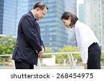 Asian senior businessman & young female executive bowing to each other