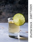 Small photo of Short of tequila anejo with lime and salt over gray metal table