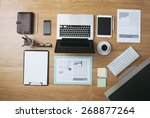 Businessman's tidy desktop and work tools with paperwork, computer, touch screen devices and stationery on a wooden surface, top view - stock photo