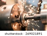 metalworking industry: finishing metal working on lathe grinder machine with flying sparks