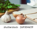 Vegetarian cooking concept. Spinach salad on wooden board, garlic, onion and pieces of dough in kitchen of cafe, restaurant. Close up. Indoor shot - stock photo