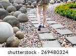 Small photo of woman walk alone on way brick in public garden
