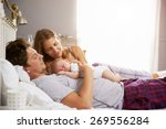 Family In Bed Holding Sleeping...