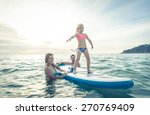Small photo of happy family teaching the daughter to stand on the surf in the ocean. concept about family, sport, active people