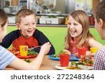 Stock photo group of pupils sitting at table in school cafeteria eating meal 272248364
