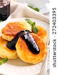 Small photo of Quark cheese fried cakes with blackberry jam on top