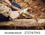 Girl cuts a stick a knife in the woods - stock photo