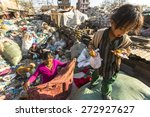 Small photo of KATHMANDU, NEPAL - CIRCA DEC, 2013: Unidentified child and his parents during lunch in break between working on dump. Only 35% of population Nepal have access to adequate sanitation.