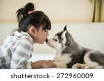 Stock photo little asian girl kissing a siberian husky puppy on bed 272960009