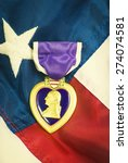 Small photo of Purple heart awarded for wounds in combat. Retro instagram look.