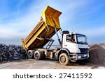 A Dump Truck Is Dumping Gravel...