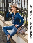 Small photo of young stylish pretty happy woman smiling and talking on her phone, dressed in denim shirt and jeans, high heel shoes, hat and backpack, sunny day, good weather, city street, cool accessorize, vacation