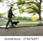 Stock photo walking the dog on the street intentional motion blur 274676297