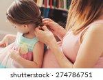 Pregnant Woman Weaving Braids...