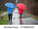 A Raincoat Dressed Couple With...