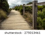 A Wooden Walkway Along A Fence...