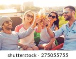 Stock photo friends and beer four young cheerful people cheering with beer and smiling while sitting at the 275055755