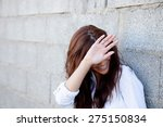 Stock photo shy brunette girl covering her face with a grey wall of background 275150834
