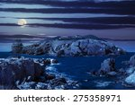 fairytale composite of rocky shore and island with hills and castle with red roofs at night in full moon light - stock photo