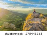 Woman Meditating On Top Of A...