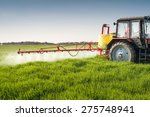 Tractor Spraying Wheat Field...