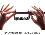 "Small photo of Color horizontal shot of two hands holding a caliper and measuring the word ""ignorance""."