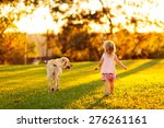 Stock photo cute little child adorable girl with curly hair and her dog yellow labrador walking away into the 276261161