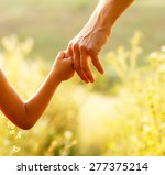 a parent holds the hand of a... | Shutterstock . vector #277375214