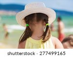 A Child In A White Hat Admirin...