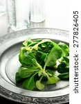 Small photo of Summer styled, brightly lit image of a fresh Lamb lettuce salad on an antique pewter plate against a light background. Copy space.