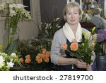 Florist holding a bouquet of flowers in her shop - stock photo