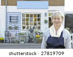 Florist standing outside her shop smiling at camera - stock photo