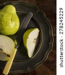 Small photo of Fresh green pears on a distressed wooden table. One of the pears has been sliced with a vintage knife and placed on a pewter plate.