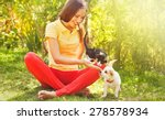 Stock photo woman playing with her can and dog outdoors 278578934