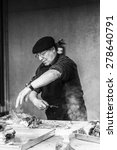 Small photo of PATAGONIA, CHILE - NOV 6, 2014: Unidentified Chilean man preapares a traditional national food of Chile Asado. Chilean people are of mixed Spanish and Amerindian descent